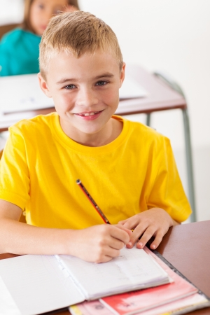 adorable elementary student in classroom writing classwork