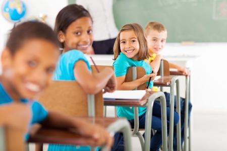 classroom teacher: gruppo di studenti della scuola primaria in aula guardando indietro