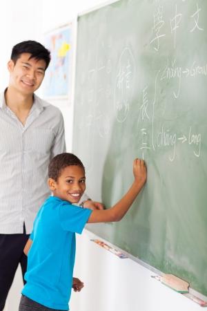 estudiantes adultos: la escuela primaria profesor de lengua china y estudiante de pizarra Foto de archivo