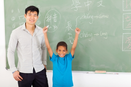 asian teacher: happy african boy with hands up after writing answer on chalkboard Stock Photo