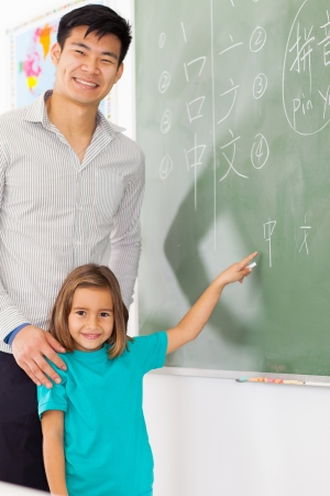 preschool girl with teacher pointing chinese language answer on chalkboard photo