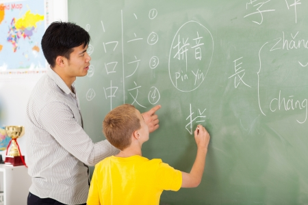 chinese word: friendly elementary school teacher helping young boy writing chinese on chalkboard