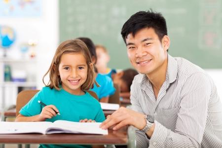 educadores: maestro cuidando escuela primaria ayudar a los estudiantes en el aula