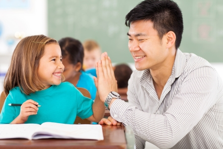 an elementary: cheerful elementary school teacher and student high five in classroom