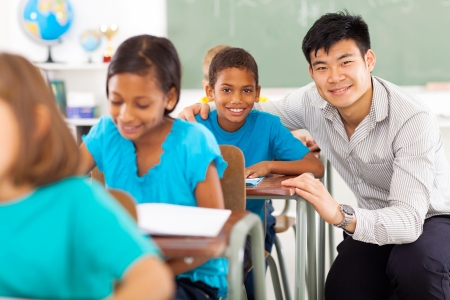portrait of happy primary teacher helping student in classroom photo