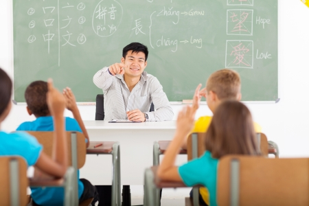 language school: handsome young teacher teaching chinese language in elementary classroom