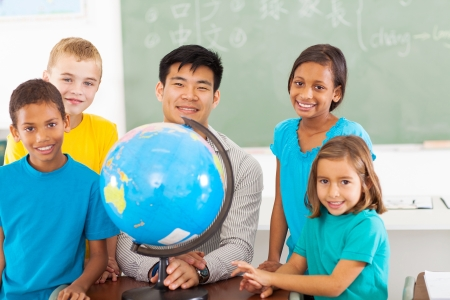 cheerful primary school geography teacher and students with a globe photo