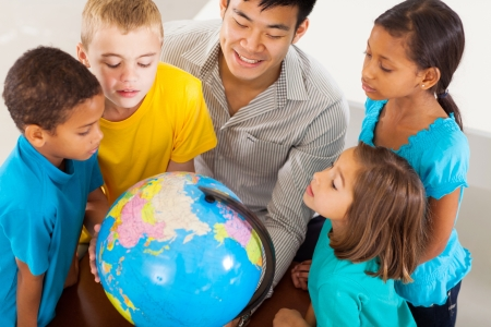 kid friendly: group of adorable students with teacher looking at the globe Stock Photo
