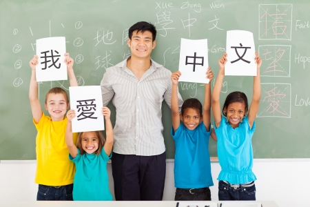 friendly male chinese teacher with group multiracial primary students holding papers saying i love chinese photo