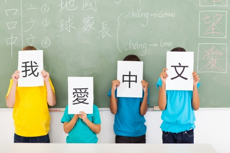 group of primary school students holding paper saying i love chinese photo