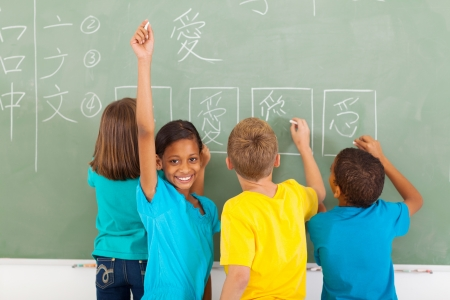 child studying: happy schoolgirl after writing chinese on blackboard