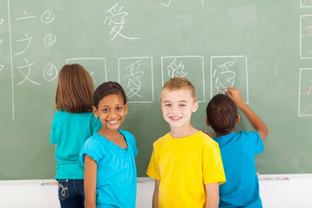 language school: cheerful elementary school students after writing chines on chalkboard