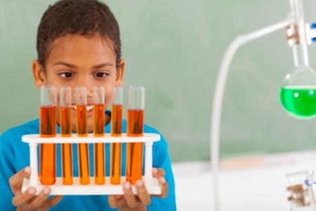 science class: cute male primary school student in science class holding tubes