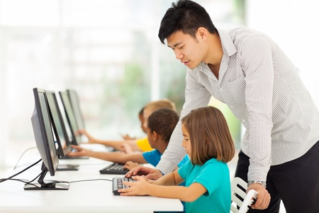 chinese american: young elementary school teacher teaching students in computer room