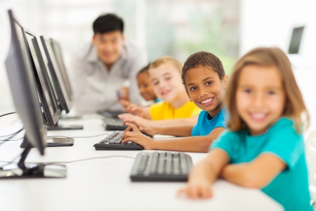 multiracial children: smiling group children in computer class with teacher on background Stock Photo