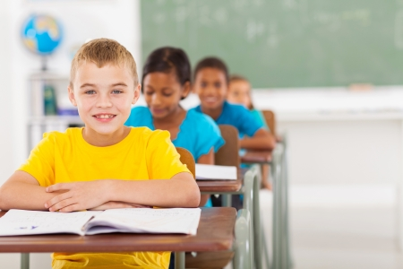 elementary students: cute elementary schoolboy with classmates in classroom Stock Photo
