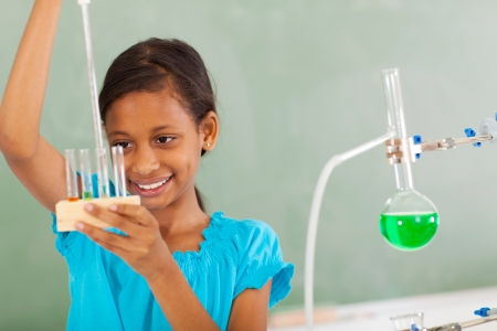 beautiful elementary student working with liquid in chemistry class photo