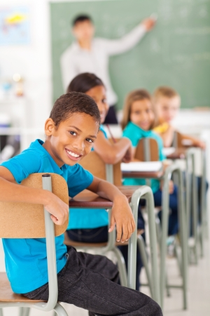 learners: smiling elementary school boy in classroom looking back