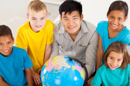 learners: smiling geography teacher with group of adorable primary students Stock Photo