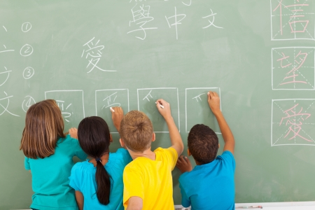 rear view of elementary school students learning chinese writing on chalkboard photo