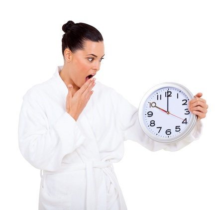 overslept: overslept woman in bathrobe looking at the clock