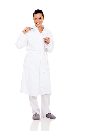 beautiful woman in pajamas brushing teeth isolated on white photo
