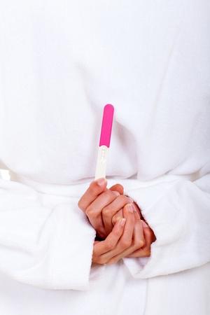 test de grossesse: femme dans un test de grossesse de se cacher derri�re son dos peignoir Banque d'images
