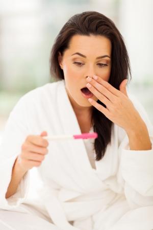 prueba de embarazo: mujer joven quedó sorprendida cuando su prueba de embarazo que muestra el resultado positivo Foto de archivo