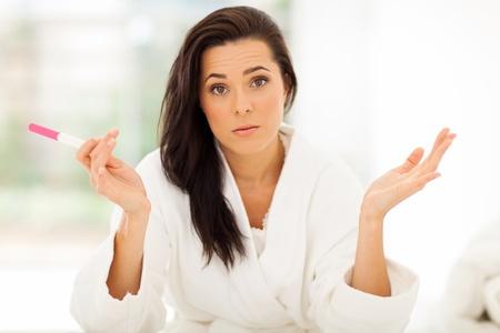 희망이없는 느낌이 임신 테스트를 들고 슬픈 젊은 여자