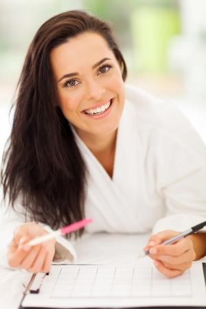 kalendarz: wesoła kobieta, leżąc na łóżku na piśmie kalendarz ciąża jej wynik Zdjęcie Seryjne