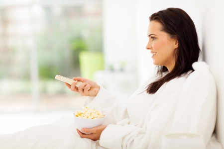 home cinema: smiling young woman watching tv and eating popcorn on bed