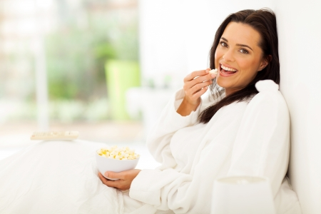 popcorn bowls: beautiful woman in bed eating popcorn and watching movie