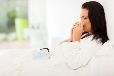 enfermos: mujer enferma en la cama que sopla su nariz