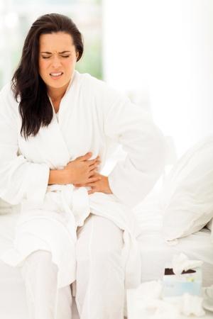 constipated: mujer joven que tiene dolor de est�mago en el hogar