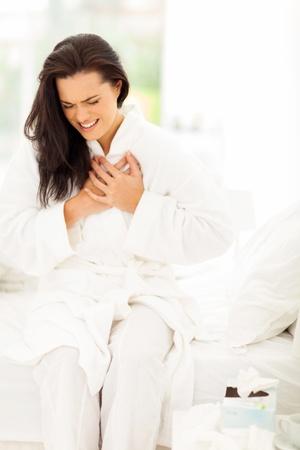 attacco cardiaco: giovane donna in pigiama con attacco di cuore Archivio Fotografico