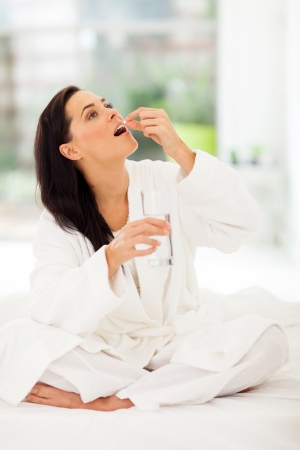 beautiful woman drinking medicine at home photo