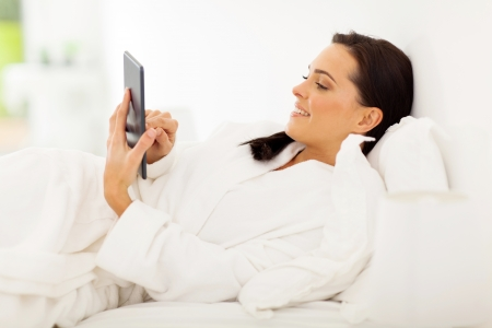 woman lying in bed: gorgeous woman using tablet computer on bed at home