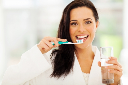 close up portrait of cute woman brushes her teeth photo