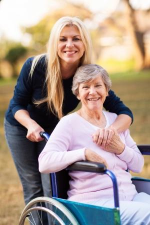 80s adult: Mujer mayor feliz en una silla de ruedas y su hija en el parque Foto de archivo