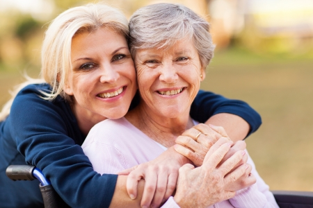 handicapped person: cheerful middle aged woman embracing disabled senior mother outdoors Stock Photo