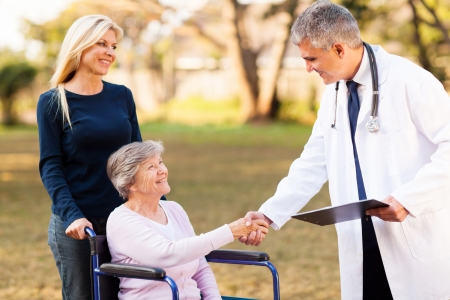 friendly male doctor handshaking with senior patient outdoors photo