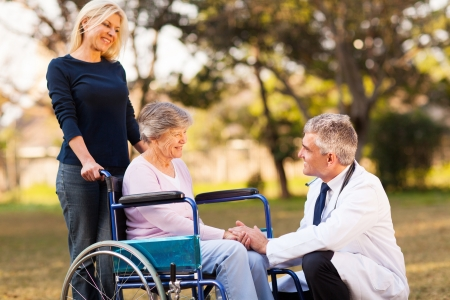 male doctor talking with handicapped senior woman at the retirement home photo