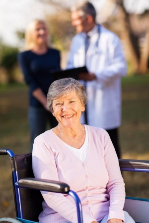smiling disabled senior woman outdoors with her daughter and doctor on background photo