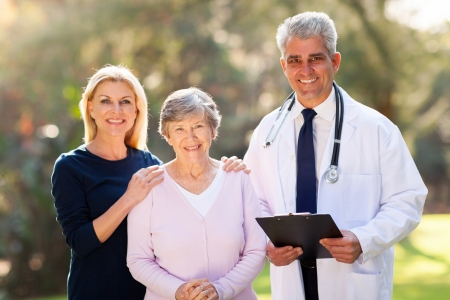 senior adult man: medical doctor standing with senior patient and her daughter outdoors