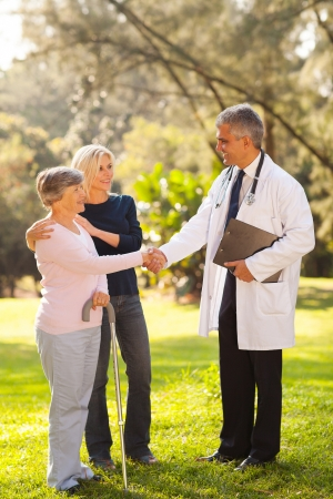 senior patient with daughter handshaking with male middle aged doctor outdoors photo