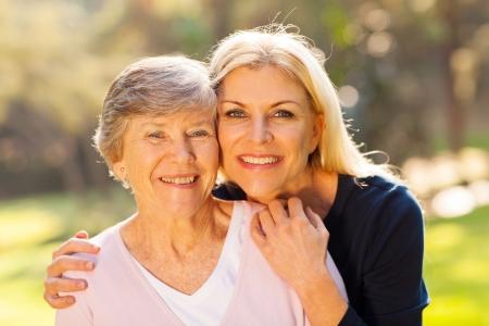 madre e hija: sonriente mujer mayor y su hija de mediana edad al aire libre retrato de detalle