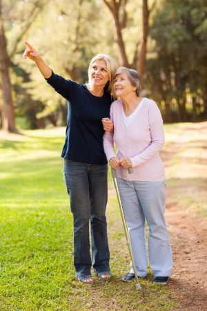 senior adult woman: loving middle aged daughter taking senior mother for a walk outdoors in forest Stock Photo