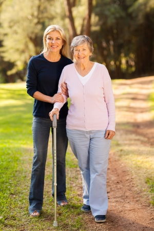 smiling senior woman and caring daughter walking in forest photo