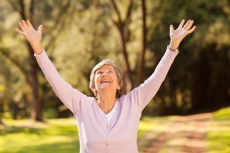 outstretched arms: healthy elderly woman looking up with arms outstretched outdoors