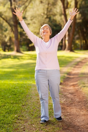 healthy retirement lifestyle concept: happy senior woman with arms outstretched outdoors photo